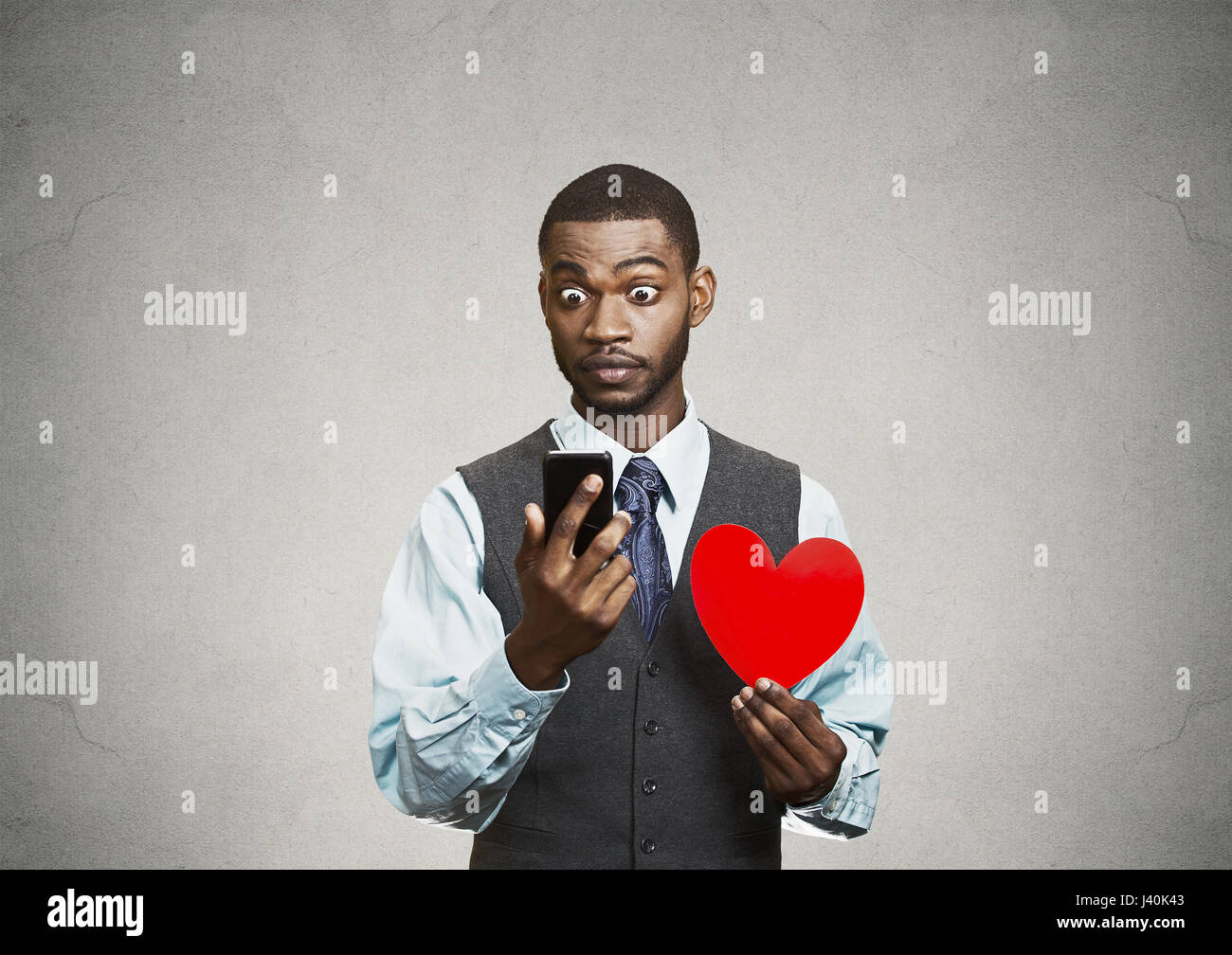 Closeup portrait puzzled young man reading breaking news on smart phone, holding red heart in his hand, isolated - Stock Image