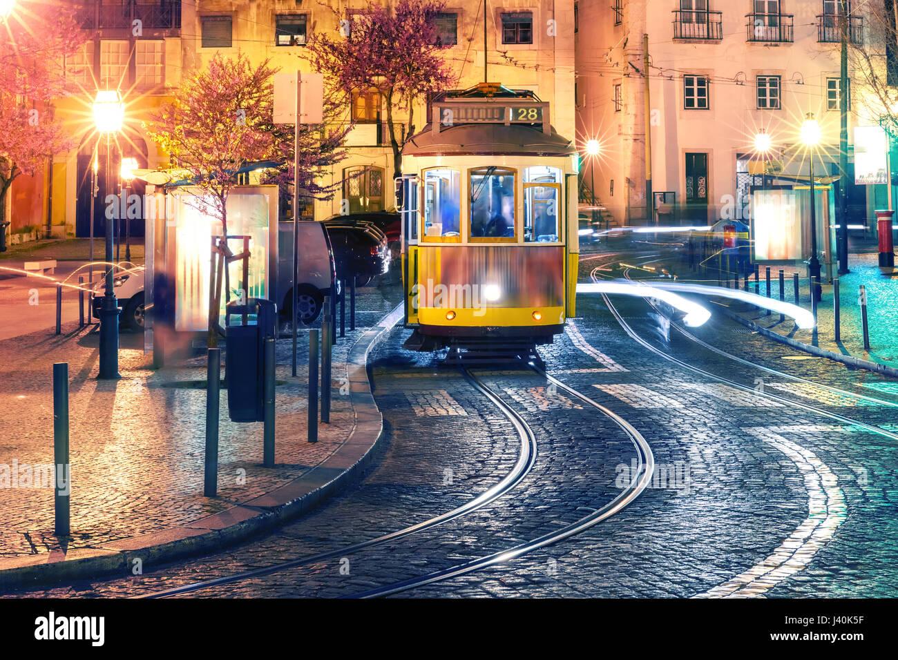 Yellow 28 tram in Alfama at night, Lisbon, Portugal - Stock Image