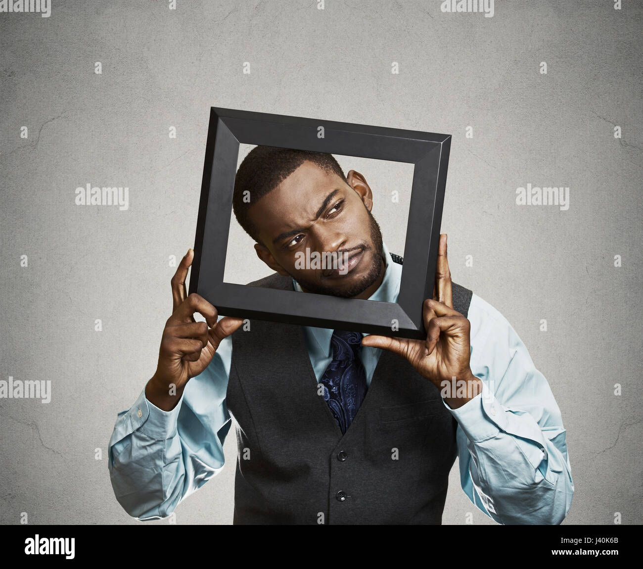 Closeup portrait young businessman executive looking up, curious surprised confused through black picture frame - Stock Image