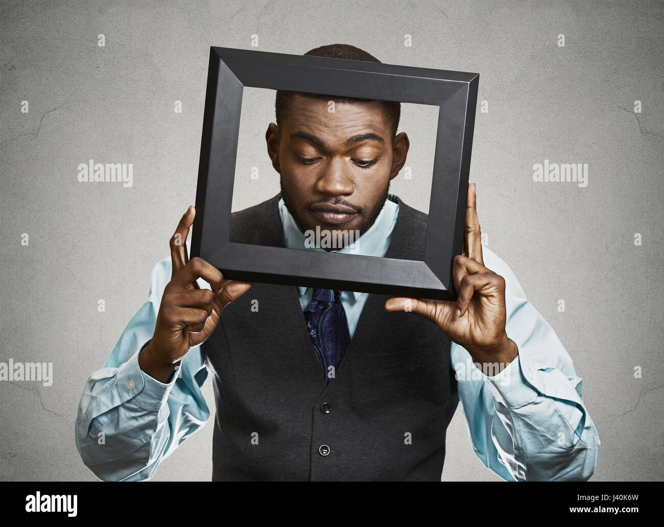 Closeup portrait businessman, executive looking down curious, surprised confused through black picture frame thinking - Stock Image