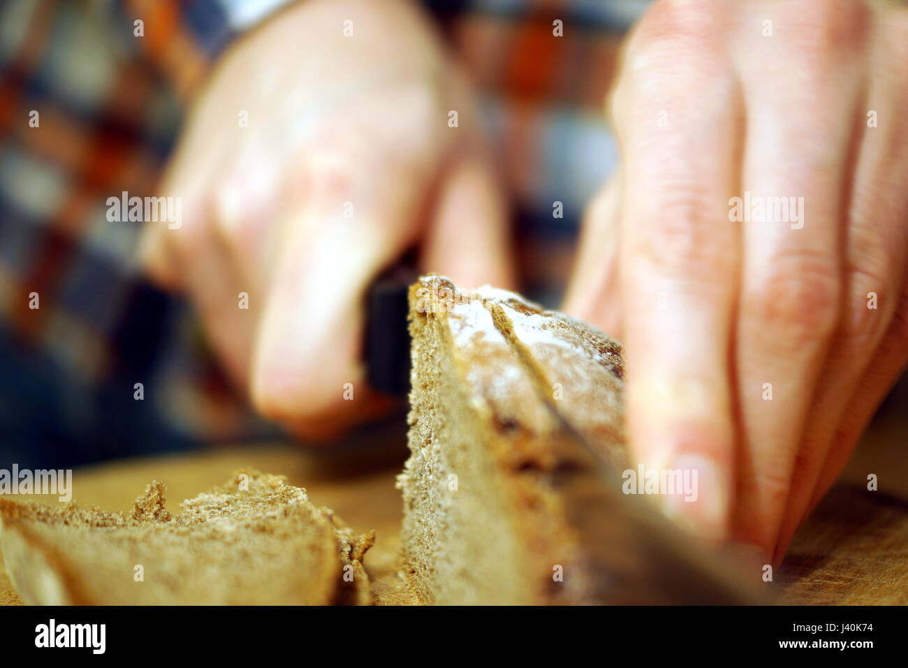 Cutting bread with a knife - Stock Image