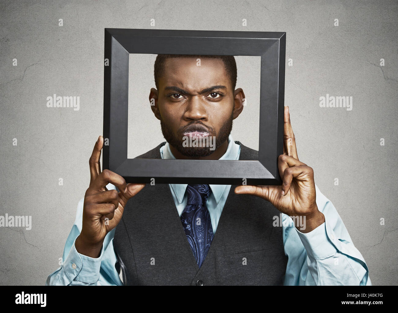 Closeup portrait businessman executive looking curious surprised confused skeptical through black picture frame - Stock Image