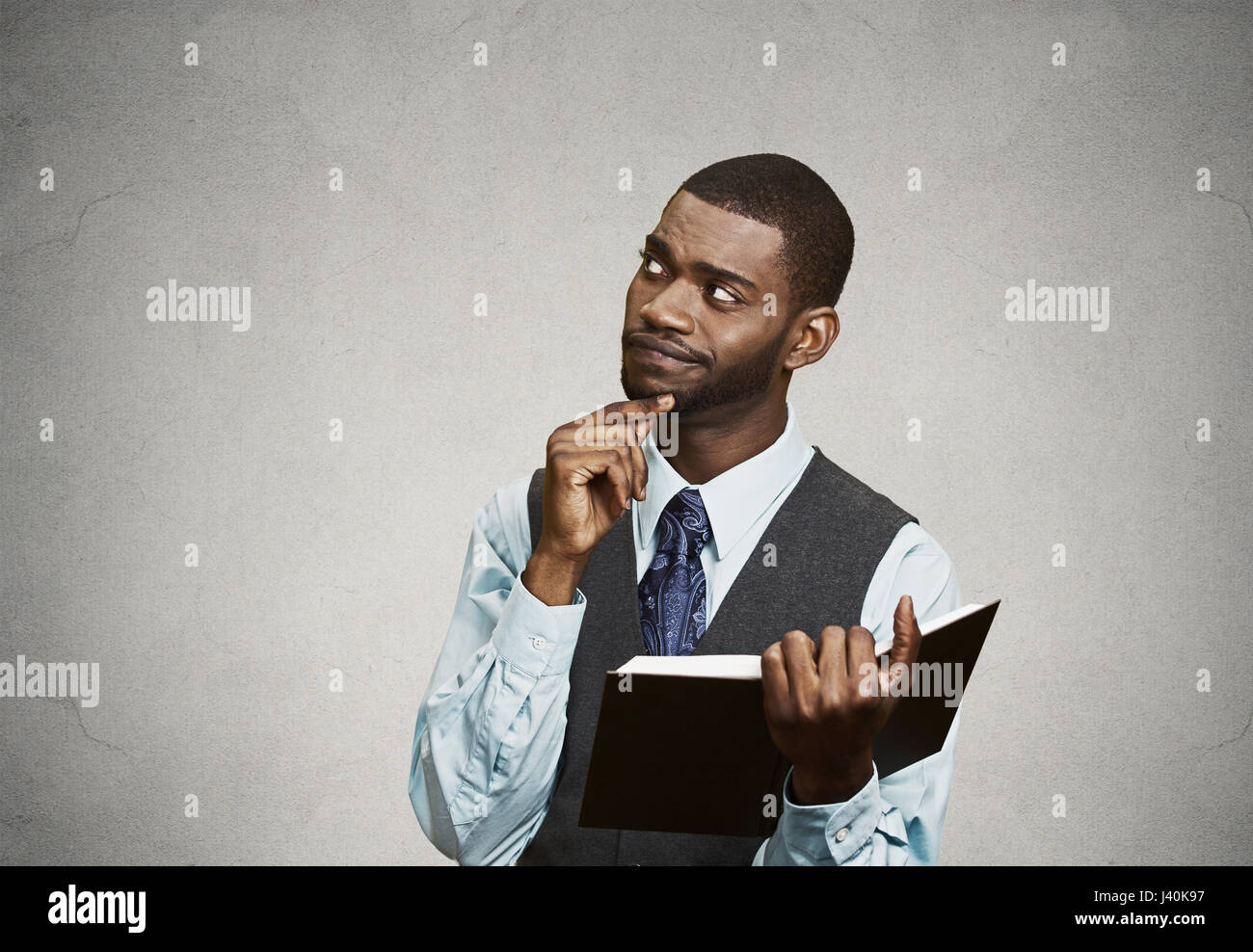 Closeup portrait confused, unhappy serious man holding, reading  book, having many questions, thinking, isolated - Stock Image