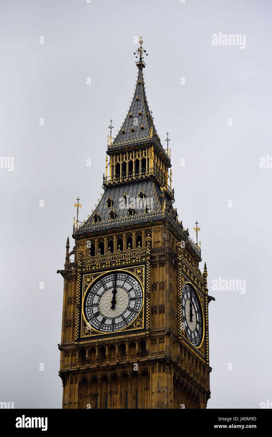 The clock of Big Ben, or Elizabeth Tower, striking mid-day twelve o'clock. Part of the Palace of Westminster, - Stock Image