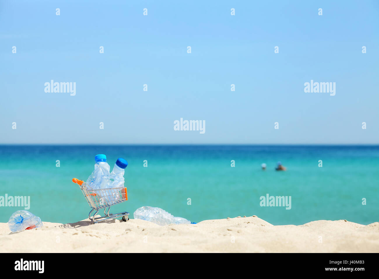 Miniature shopping cart with empty plastic bottles left by tourist on a tropical beach, environmental pollution - Stock Image