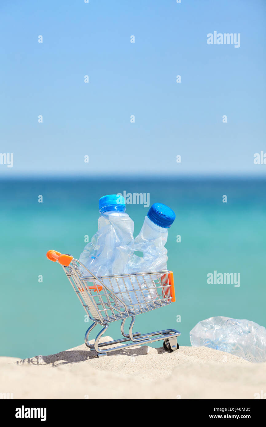 Close up picture of a miniature shopping cart with empty plastic bottles left by tourist on a beach, environmental - Stock Image