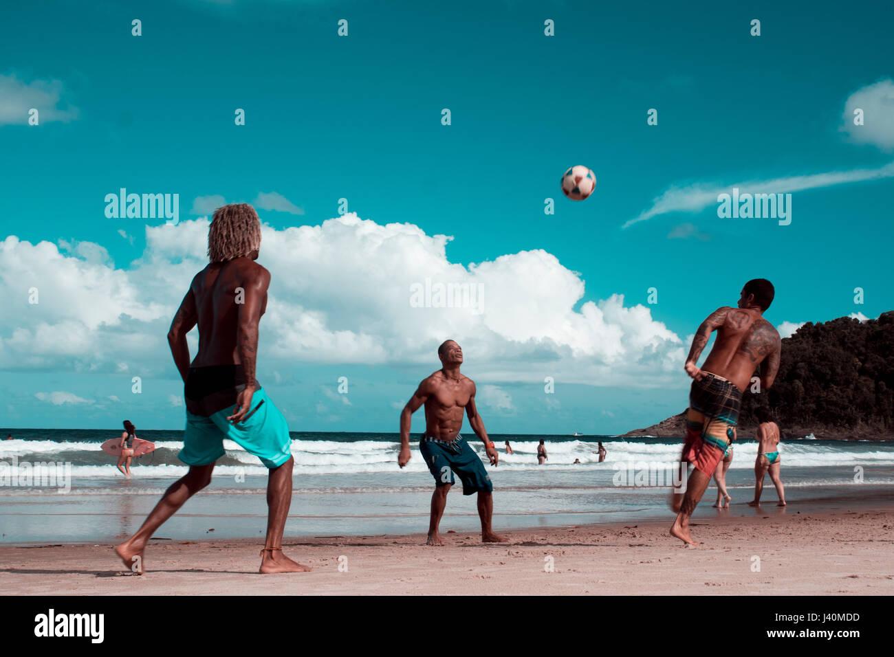 youth playing soccer and fottball on Tiririca beach, Itacare, Bahia, Brazil - Stock Image
