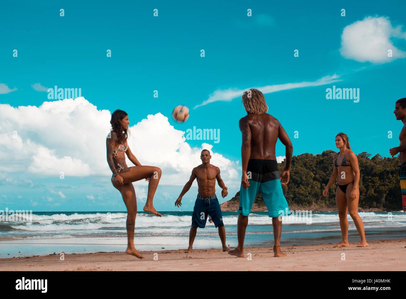 youth playing soccer and football on Tiririca beach, Itacare, Bahia, Brazil - Stock Image