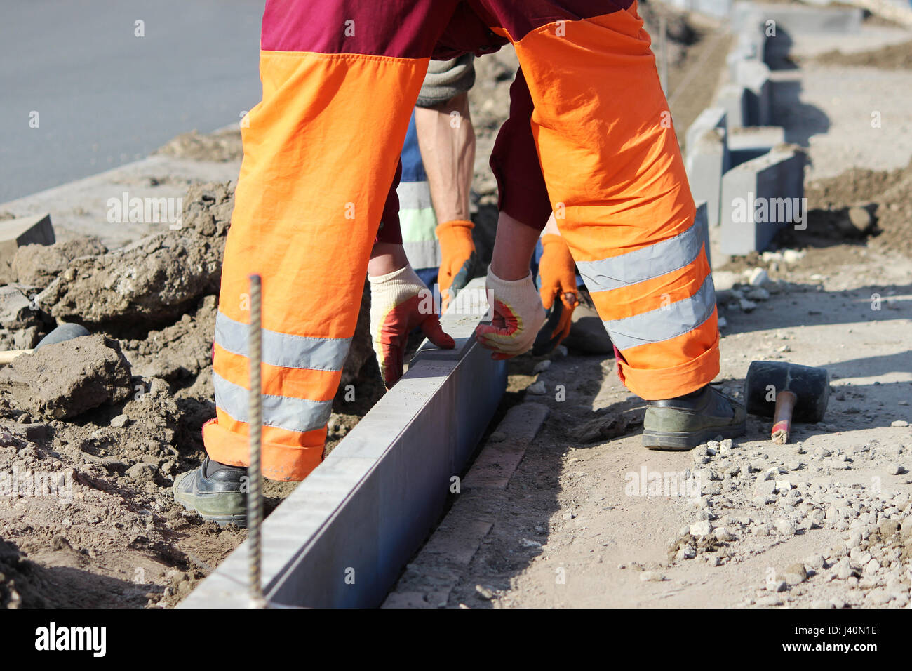 Repair of the sidewalk. Professional working masons in overalls lay curbs before laying stone paving slabs. Stock Photo