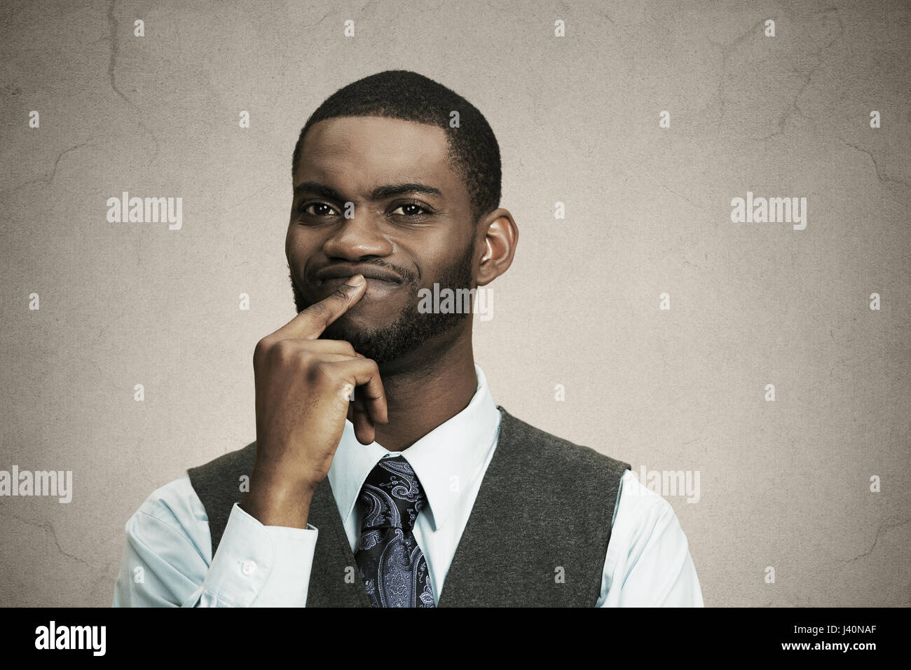 Closeup portrait young puzzled business man thinking deciding deeply about something finger on lips looking confused - Stock Image