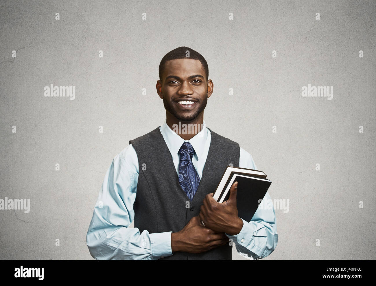 Closeup young smart, happy, smiling handsome man holding books, prepared, ready to ace his exam test finals, isolated - Stock Image