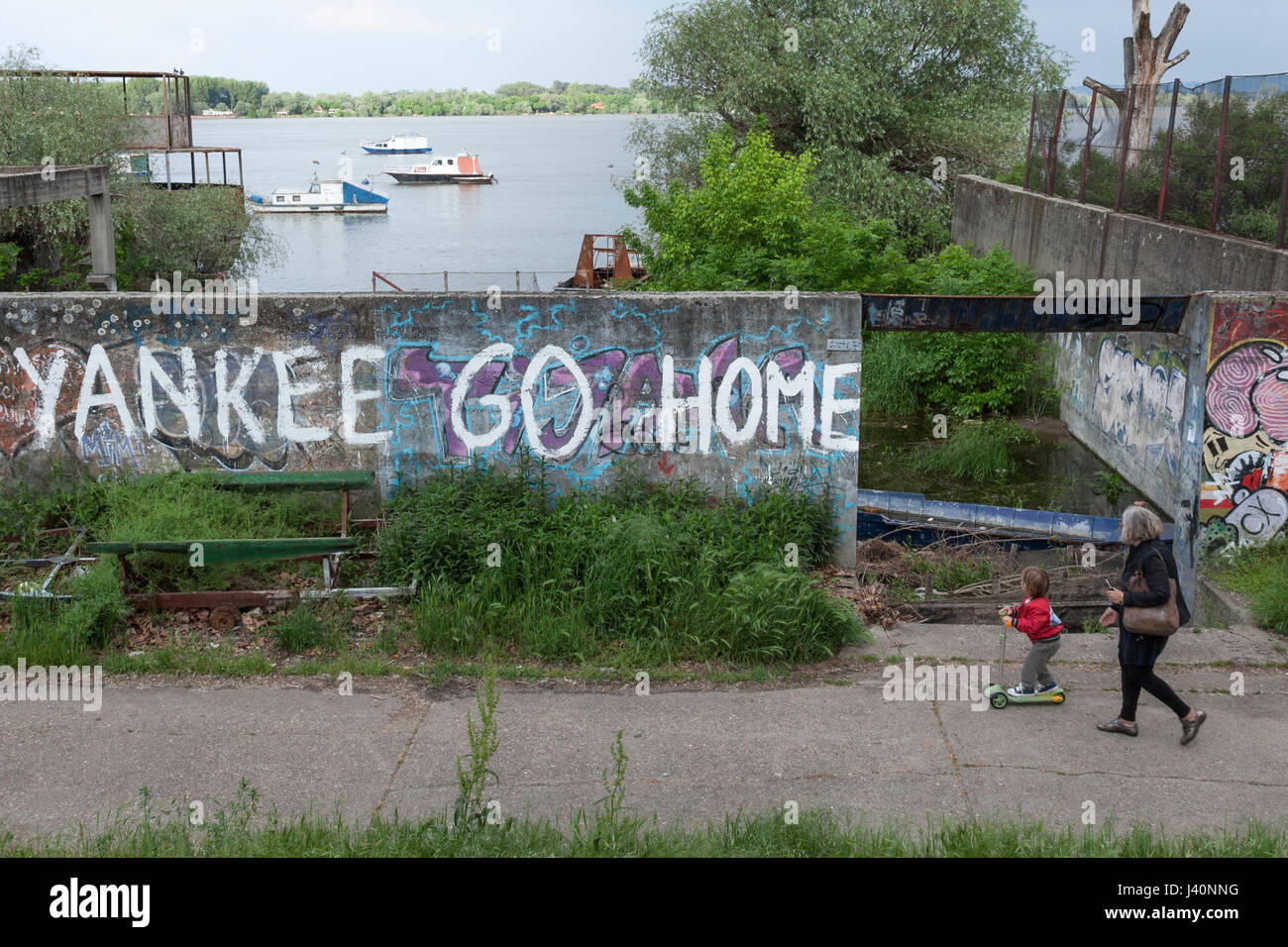 BELGRADE, SERBIA - MAY 8, 2017: Old woman and her grandaughter passing by a wall with an anti-american inscription - Stock Image