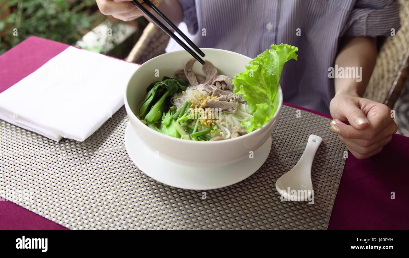 Woman eat traditional Vietnam Pho Bo beef noodle soup in restaurant