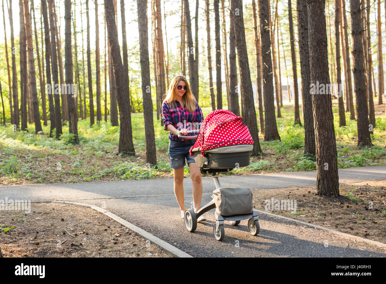 237409c7d3bf Woman Pushing Baby In Buggy Stock Photos   Woman Pushing Baby In ...