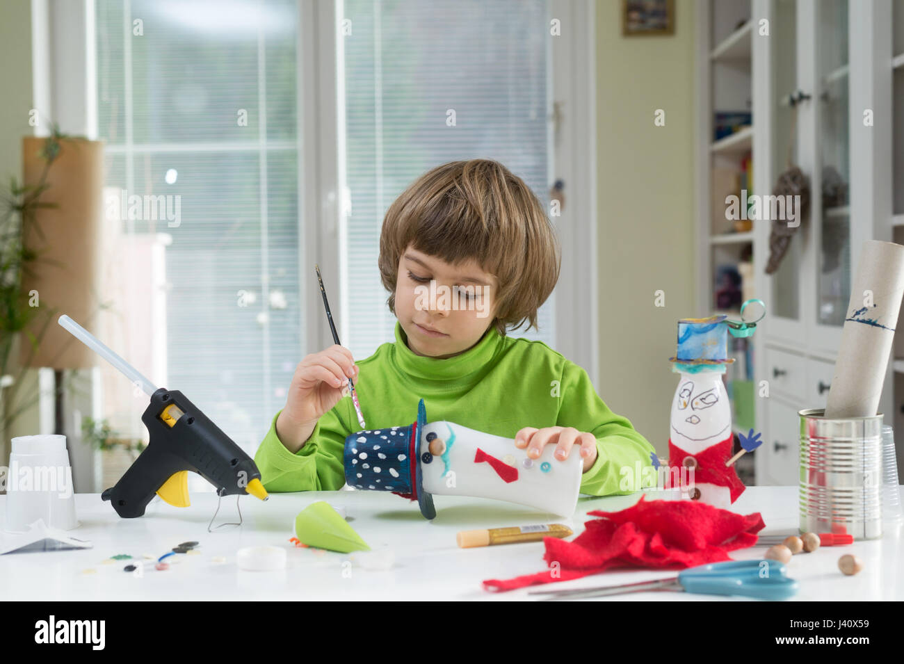 Little boy being creative making homemade do it yourself toys out of little boy being creative making homemade do it yourself toys out of yogurt bottle and paper supporting creativity learning by doing hand craft he solutioingenieria Choice Image