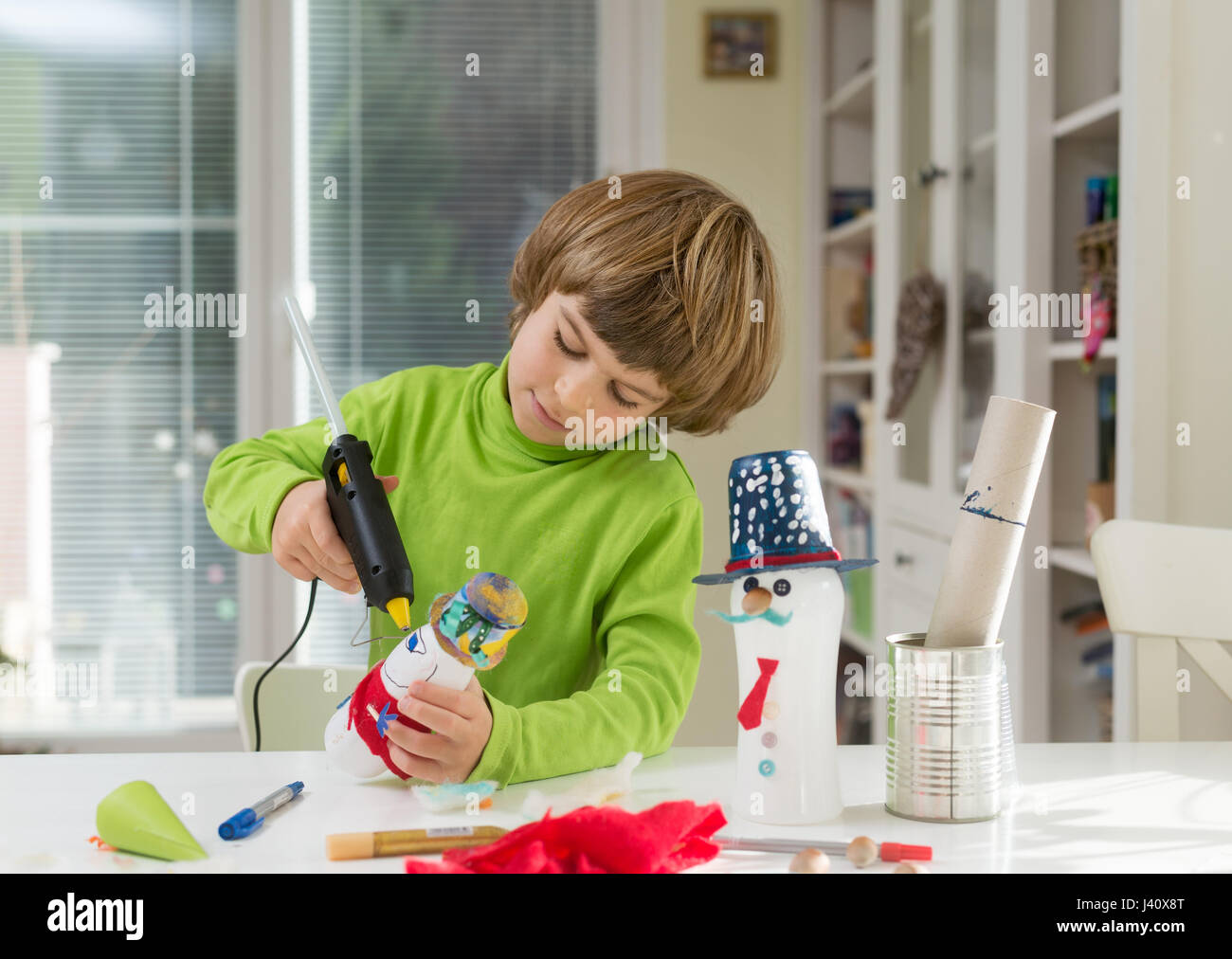 Little boy being creative making do it yourself toys out of yogurt little boy being creative making do it yourself toys out of yogurt bottle and paper using hot melt glue gun supporting creativity learning by doing solutioingenieria Choice Image