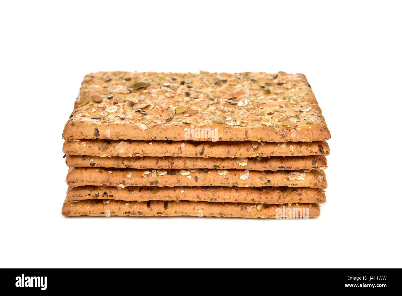 a pile of some appetizing brown crackers topped with different seeds on a white background - Stock Image