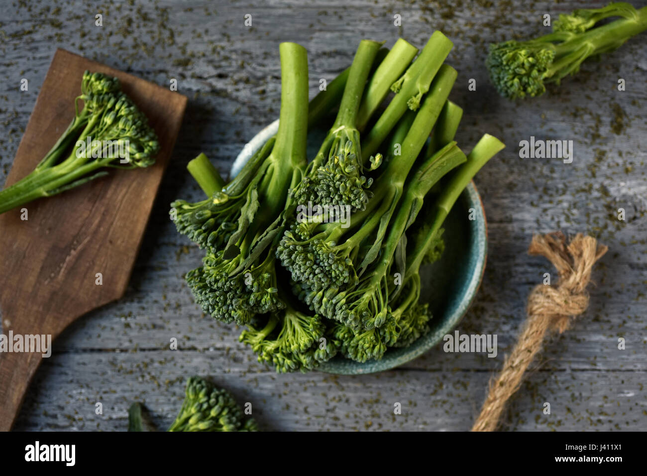high-angle shot of some stems of broccolini in a green ceramic plate placed on a gray rustic wooden table - Stock Image