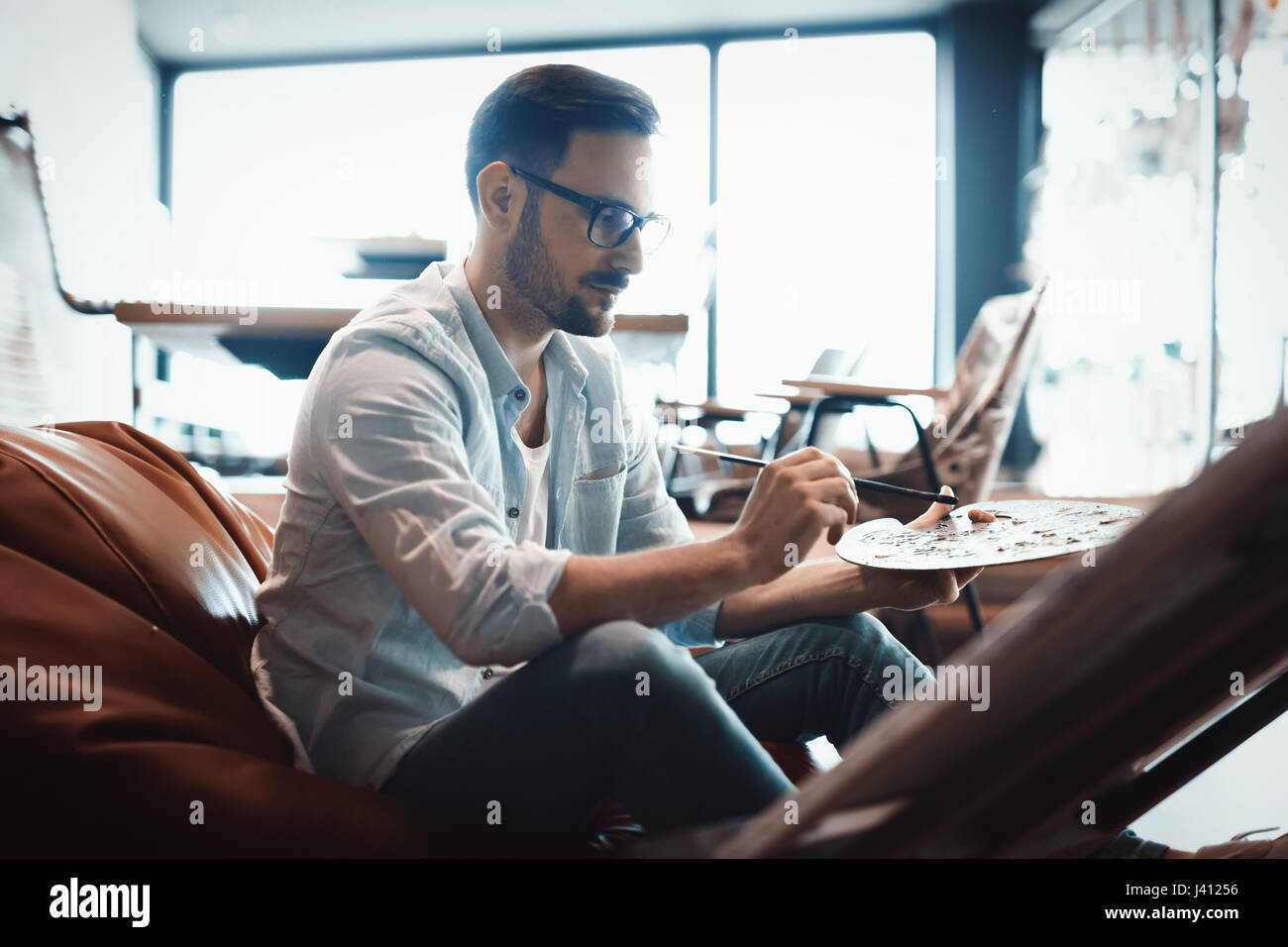 Portrait Of Male Artist Working On Painting Art In Studio - Stock Image