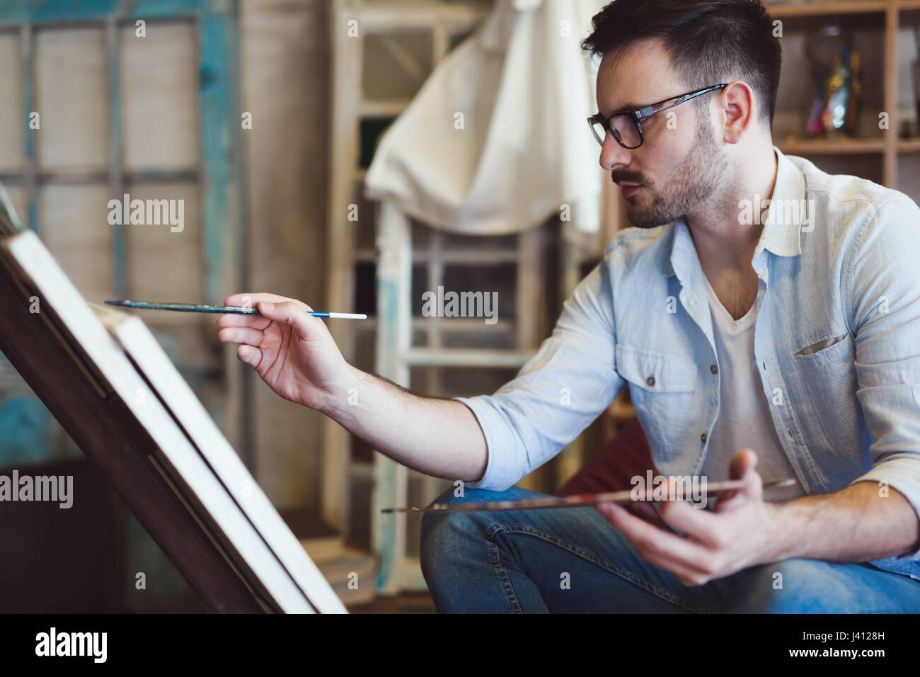 Male art school artist painting with oil on canvas in studio - Stock Image