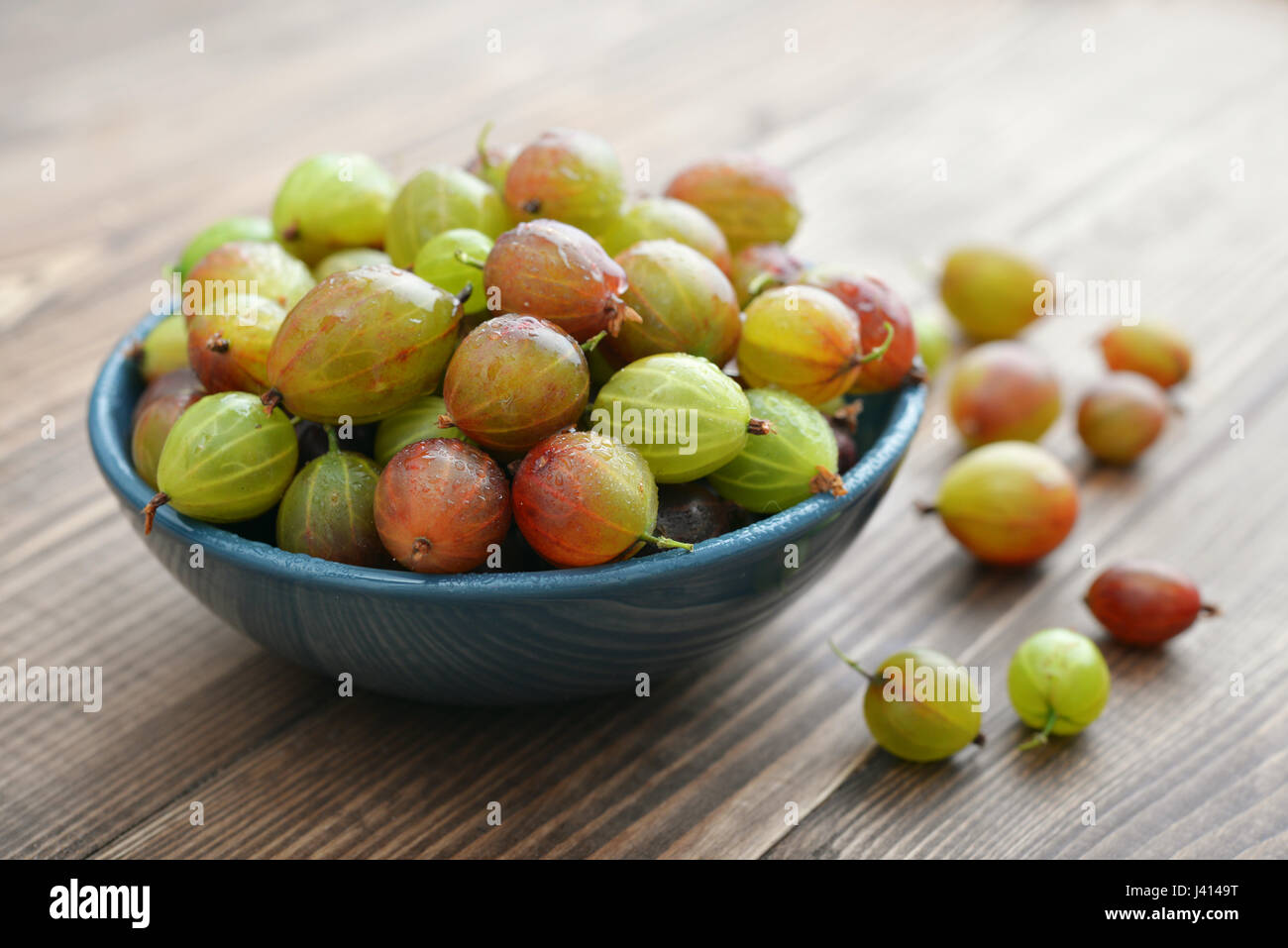 Fresh ripe gooseberry in bowl on a wooden background closeup - Stock Image