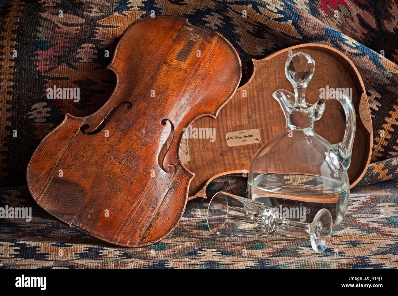 Vanitas still life, old violin in pieces, spilt glass and decanter, Persian kilim. Focus-stacked image. Stock Photo