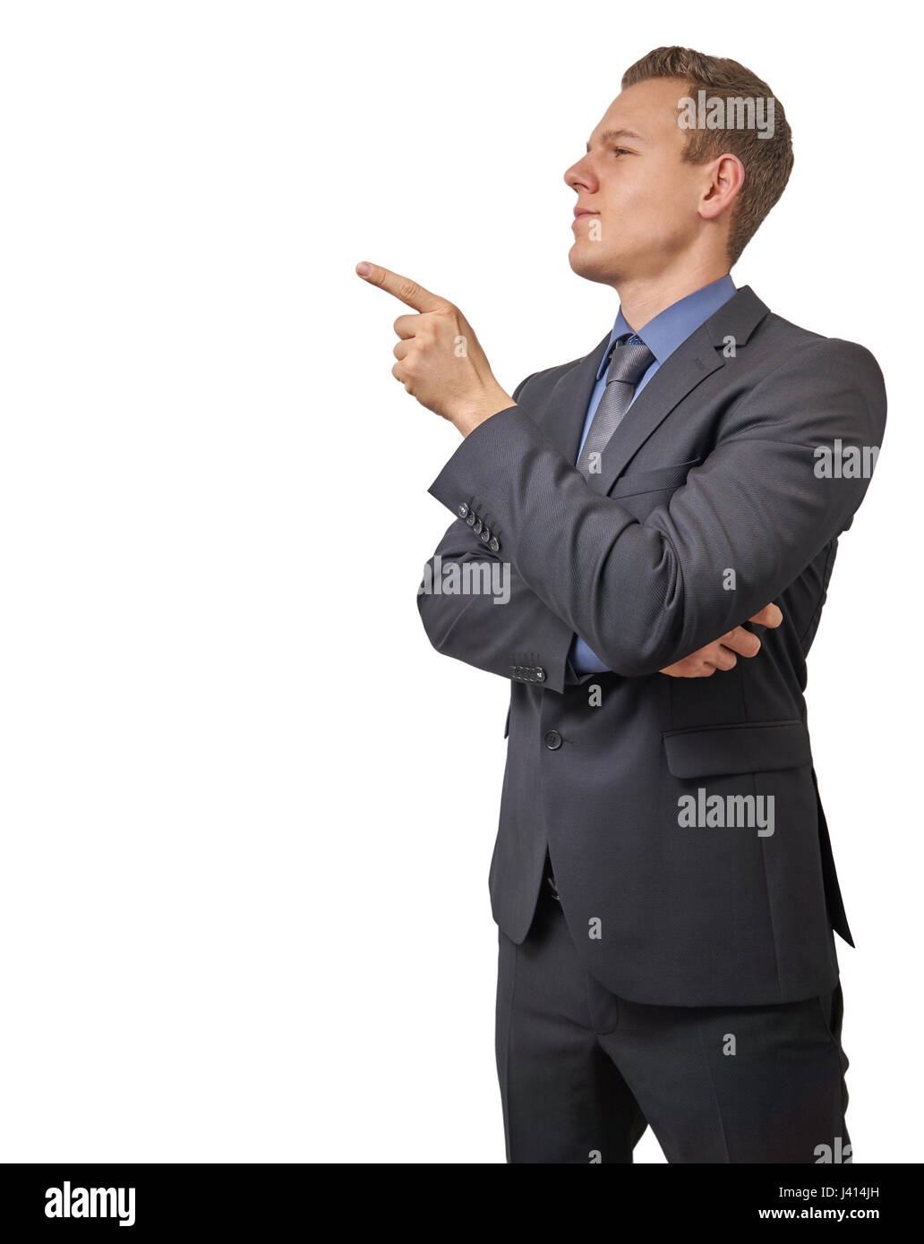 Young businessman points with his finger to his right - isolated with copyspace. Sceptical, critical or analyzing - Stock Image