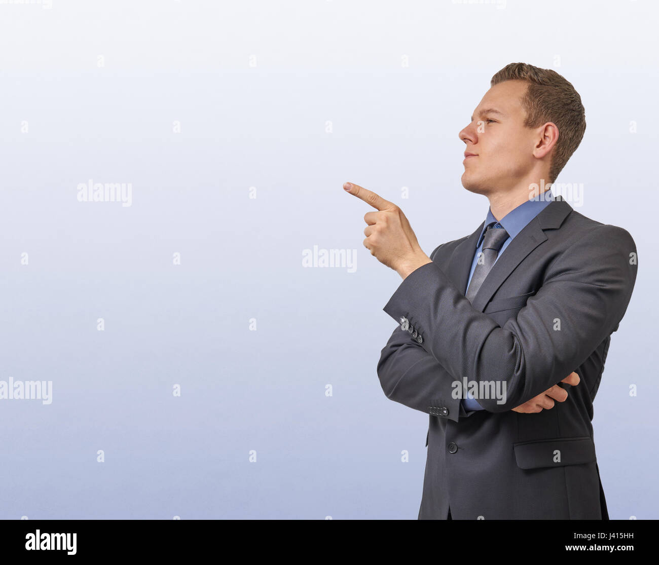 Young businessman points with his finger on the left side - isolated with copyspace. Sceptical, critical or analyzing - Stock Image