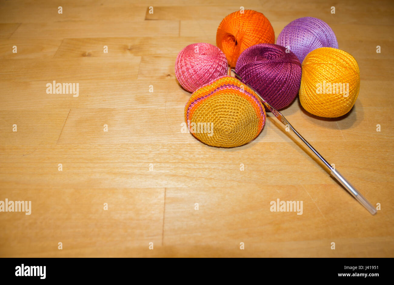 crocheting in progress and colorful cotton thread balls on the wooden background with space - Stock Image