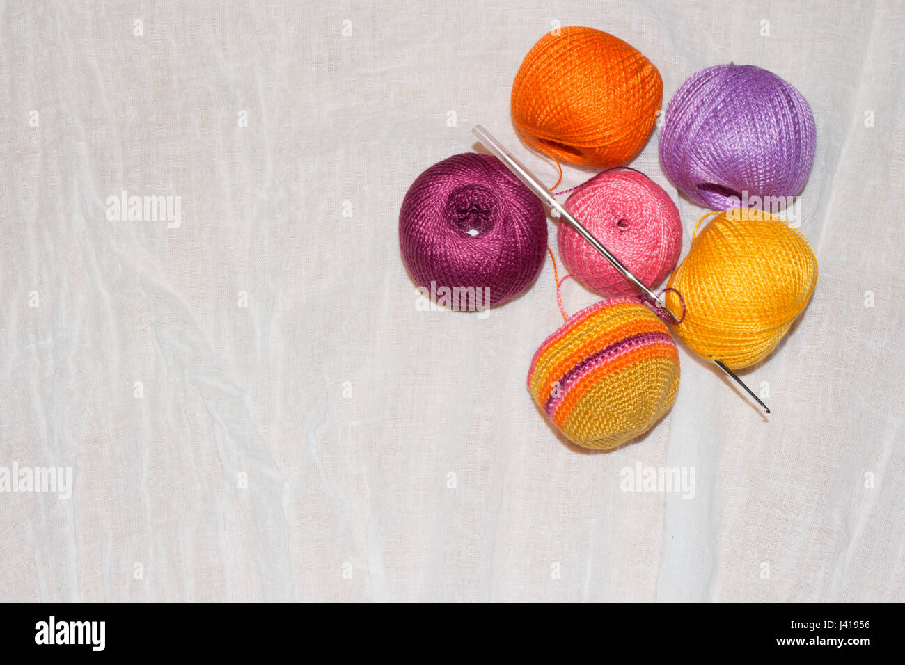 crocheting in progress and colorful cotton thread balls on the white linen background with copy space - Stock Image
