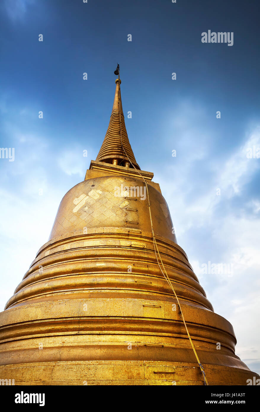 Big golden Stupa at blue cloudy sky in Wat Saket temple in Bangkok, Thailand - Stock Image