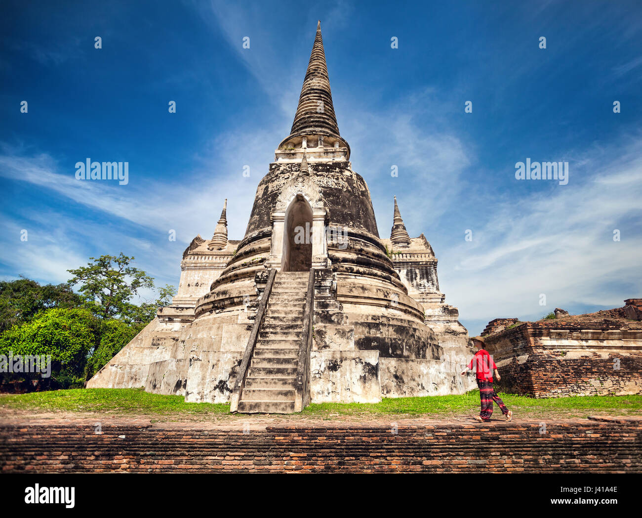 Tourist Woman in red costume walking near ancient ruined stupa in Ayutthaya Historical Park, Thailand - Stock Image