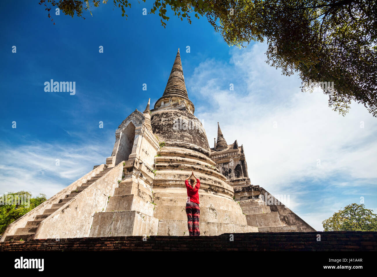 Tourist Woman in red costume praying near ancient ruined stupa in Ayutthaya Historical Park, Thailand - Stock Image