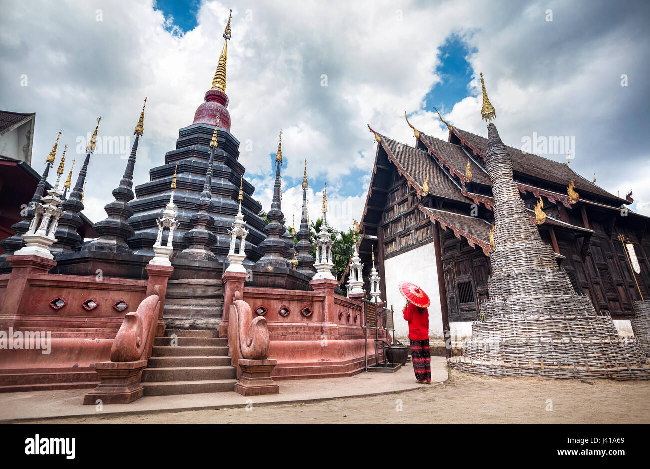 Woman with red traditional Thai umbrella looking at Black temple Wat Phan Tao made from wood in Chiang Mai, Thailand - Stock Image