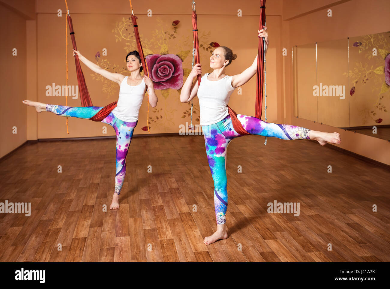 Two Young woman doing antigravity yoga stretching position at wellness studio with rose on the wall - Stock Image