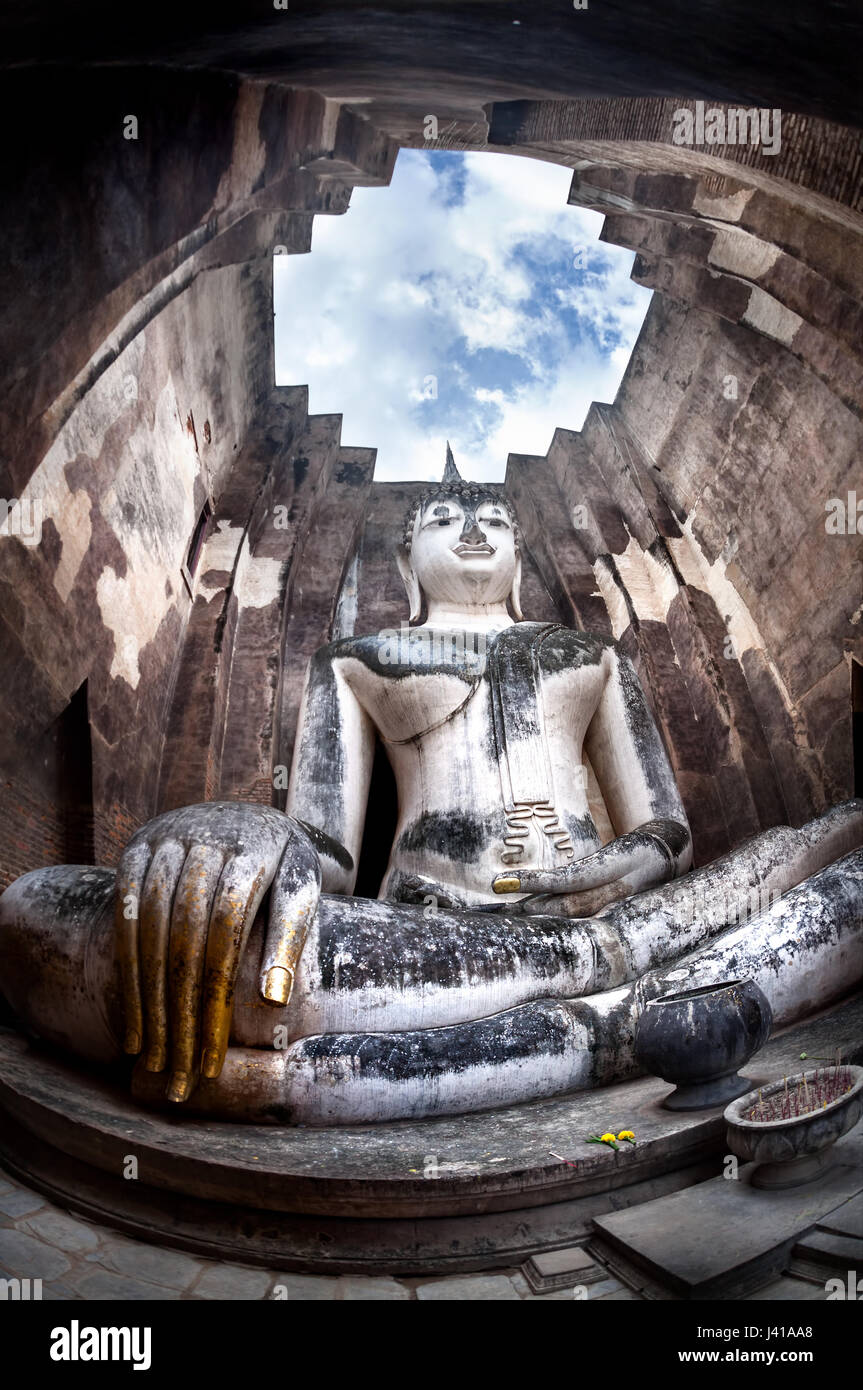 Giant statue of Buddha call Phra Achana in Wat Si Chum at Grey overcast sky in Sukhothai Historical Park, Thailand - Stock Image