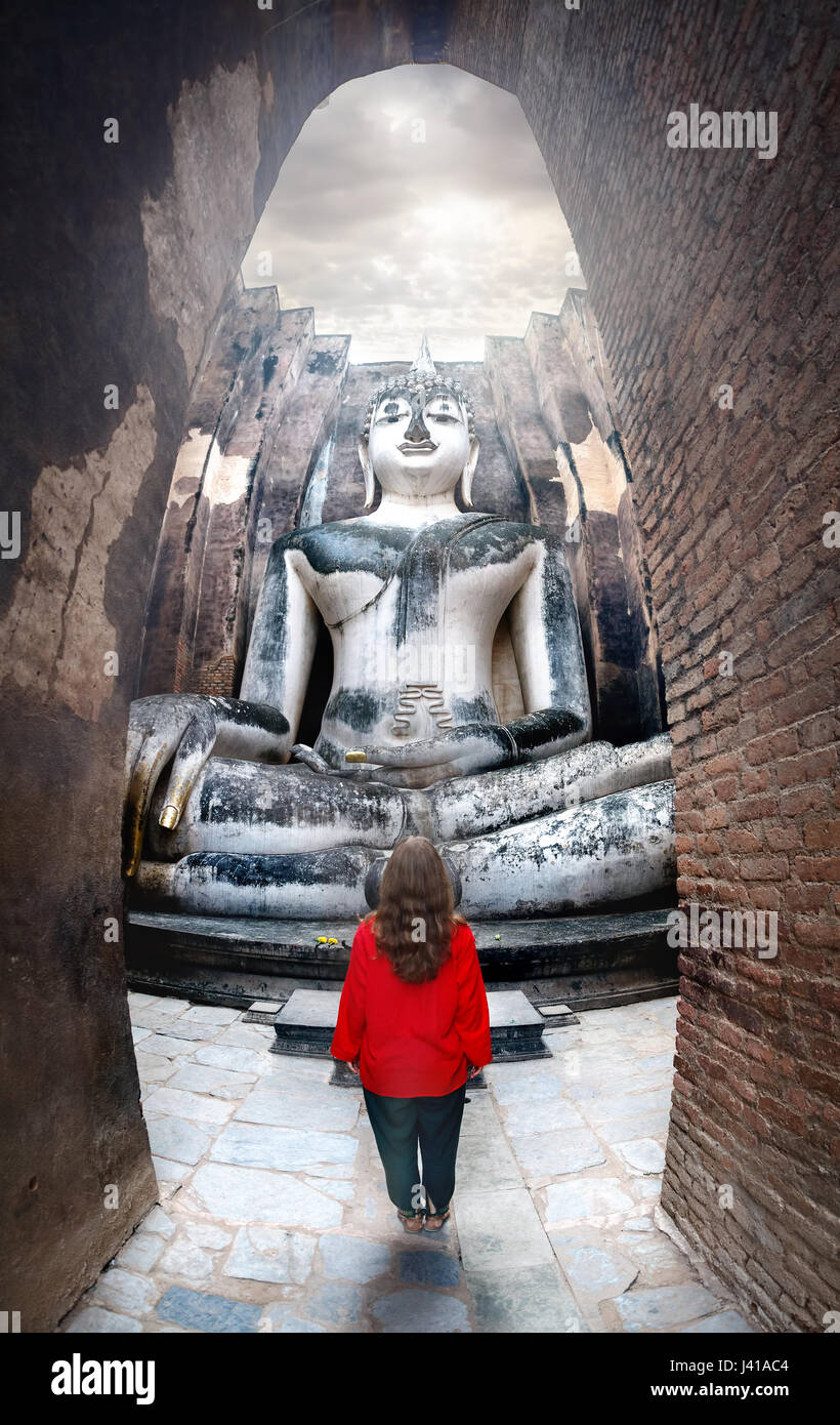 Woman in red shirt standing near giant statue of Buddha call Phra Achana in Wat Si Chum in Sukhothai Historical - Stock Image