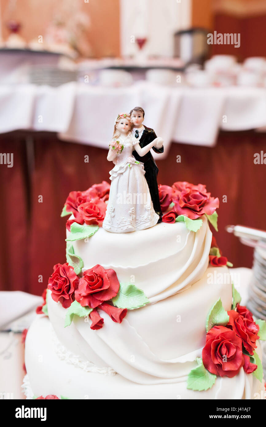 Image of a beautiful wedding cake at wedding reception. models of the newlyweds on the top tier - Stock Image