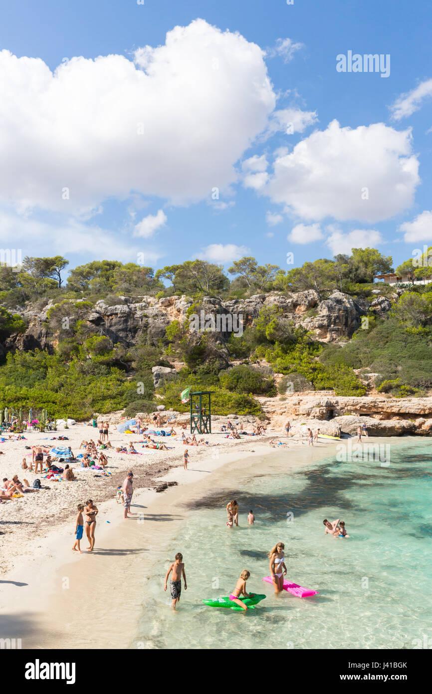 People on the beach, Cala Sa Nau, Mediterranean Sea, near Portocolom, Majorca, Balearic Islands, Spain, Europe - Stock Image