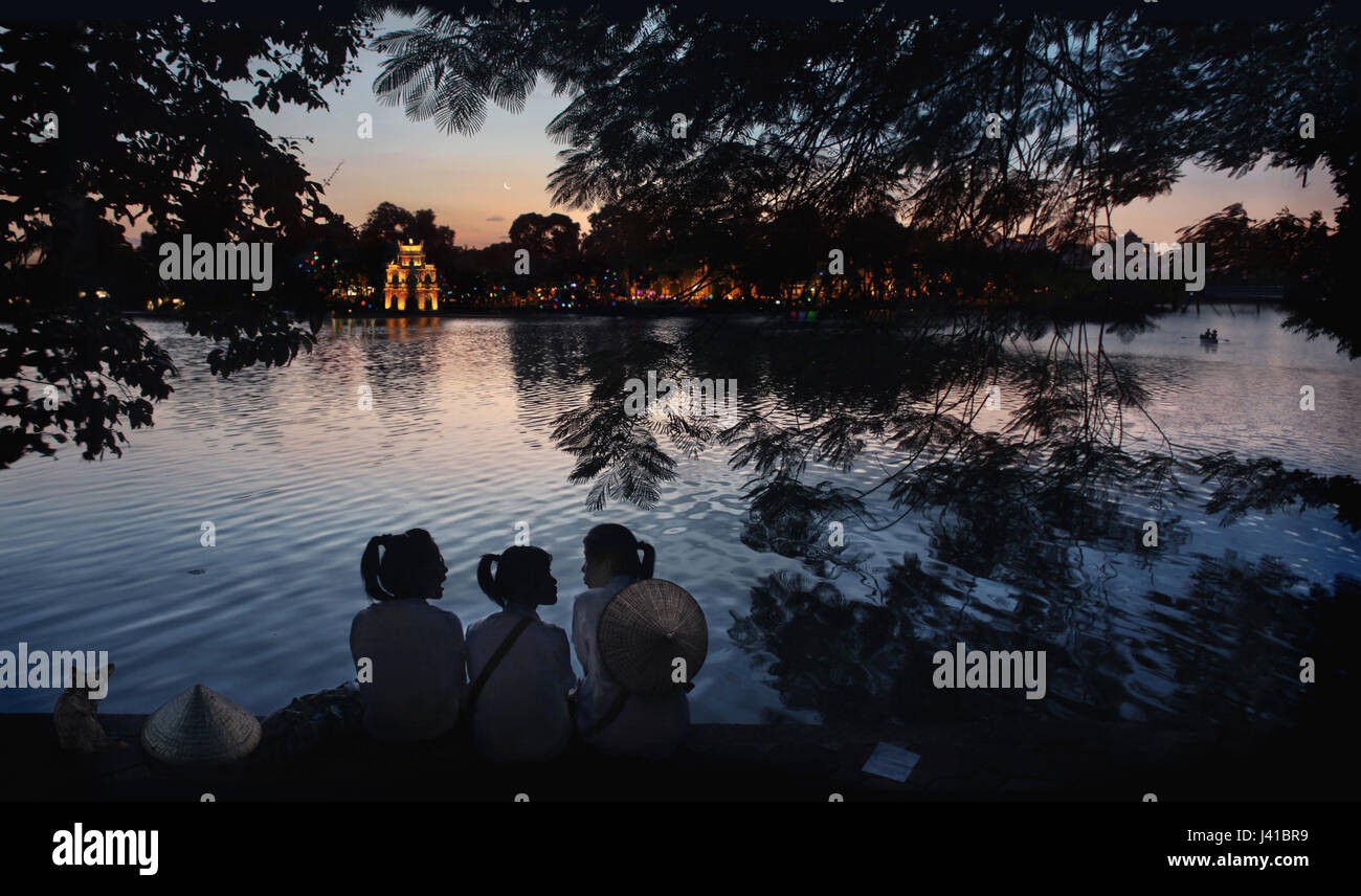 Three schoolgirls chatting on the banks of Hoan Kiem Lake with Thap Rua temple in the background, Hanoi, Vietnam, - Stock Image