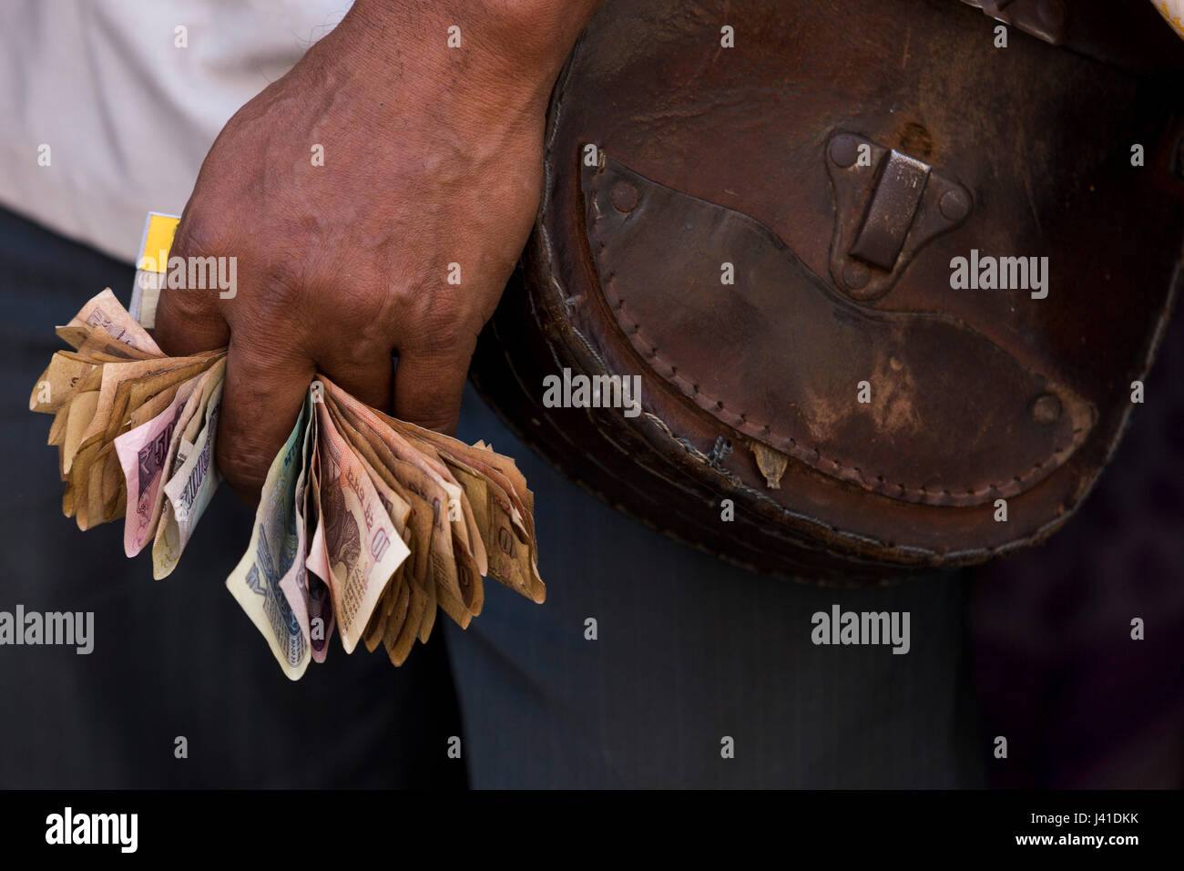 Hand of bus conductor holding banknotes, Kolkata, West Bengal, India - Stock Image