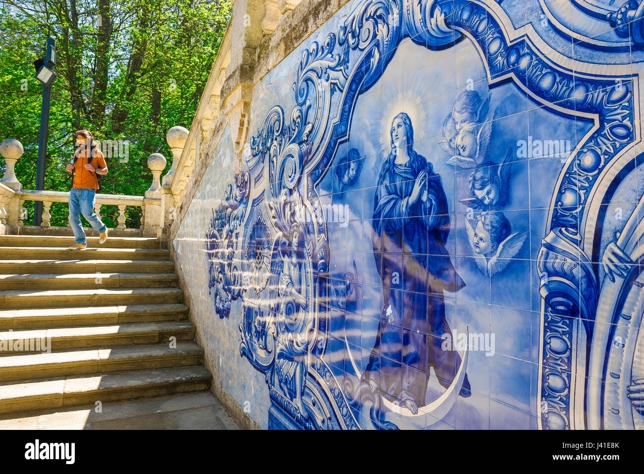 Portugal blue tiles, a man descends the azulejos decorated Baroque stairway leading to the Nossa Senhora dos Remedios - Stock Image
