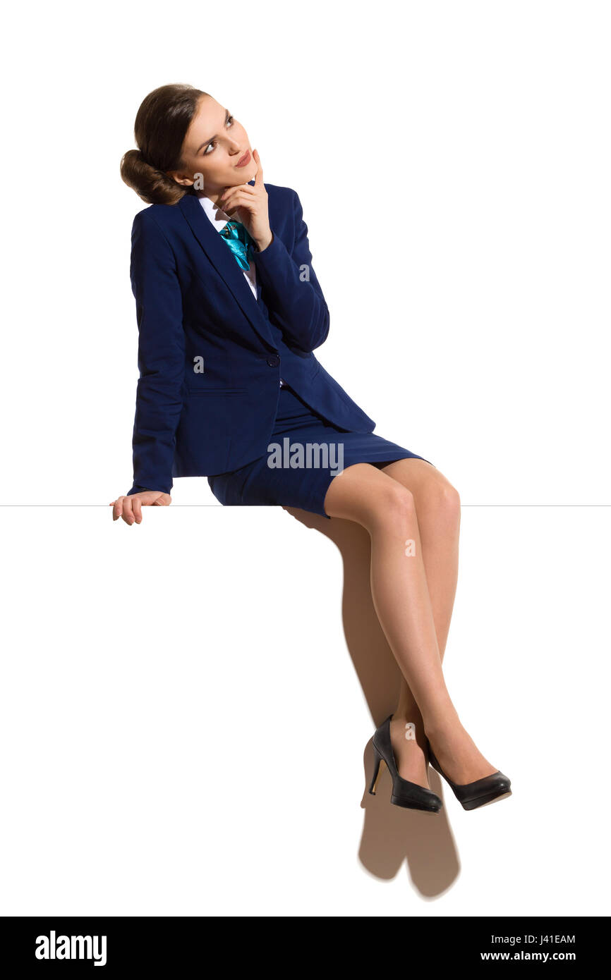 Young woman in blue formal businesswear and black high heels, sitting on a top with legs crossed, thinking and looking - Stock Image