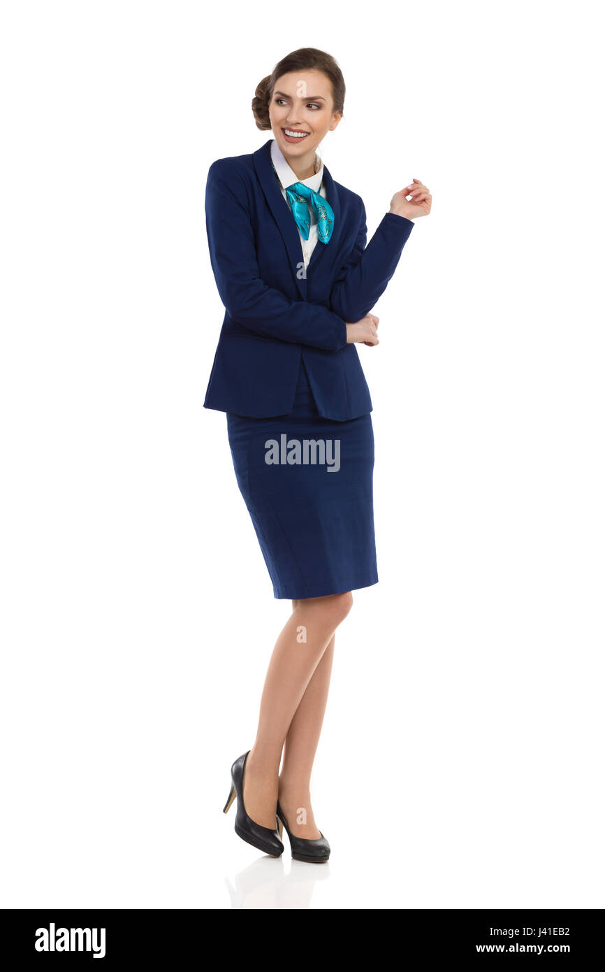 Young businesswoman in blue formalwear and high heels is smiling and looking away. Full length studio shot isolated - Stock Image