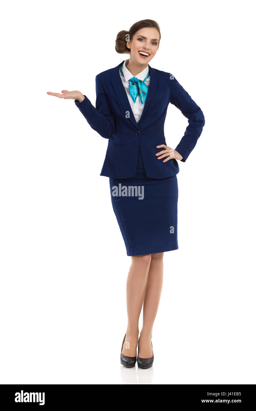 Smiling young businesswoman in blue formalwear and high heels is standing with hand raised and looking at camera. - Stock Image