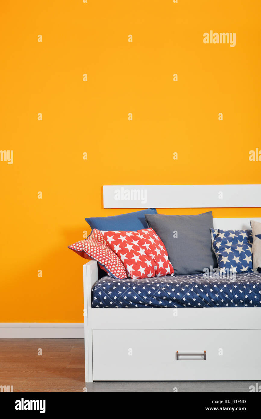 Children\'s bed bed with different color pillows against orange wall ...
