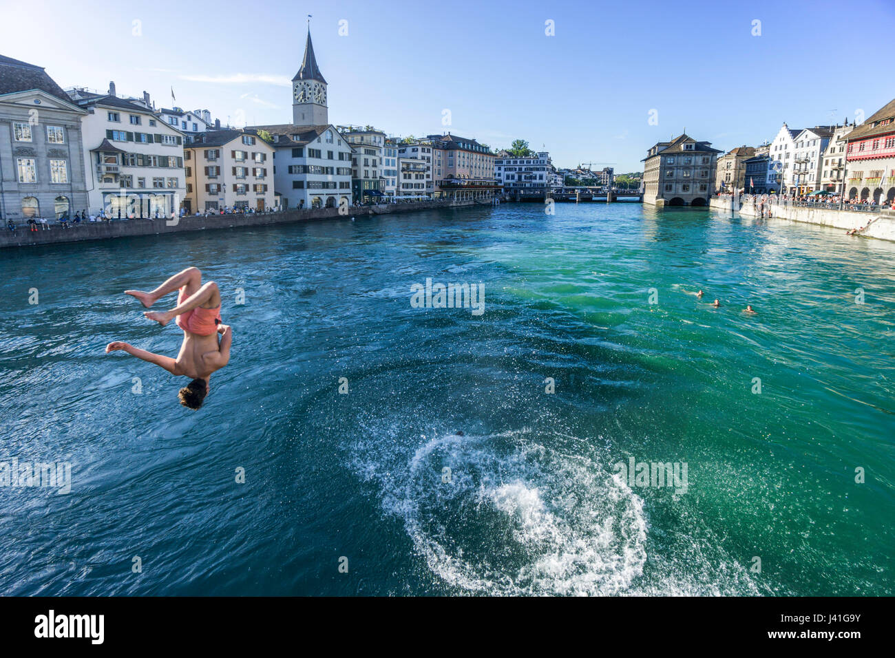 Young man jumping from Munster bridge into  river Limmat, Zurich, Switzerland - Stock Image