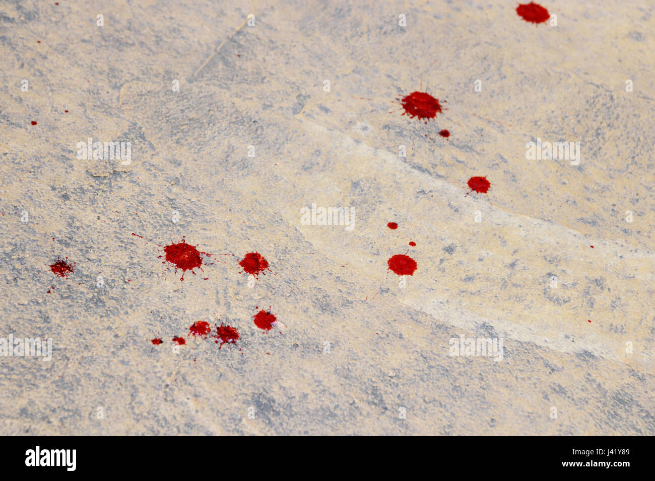 splatters of fresh human bright red blood on a concrete surface