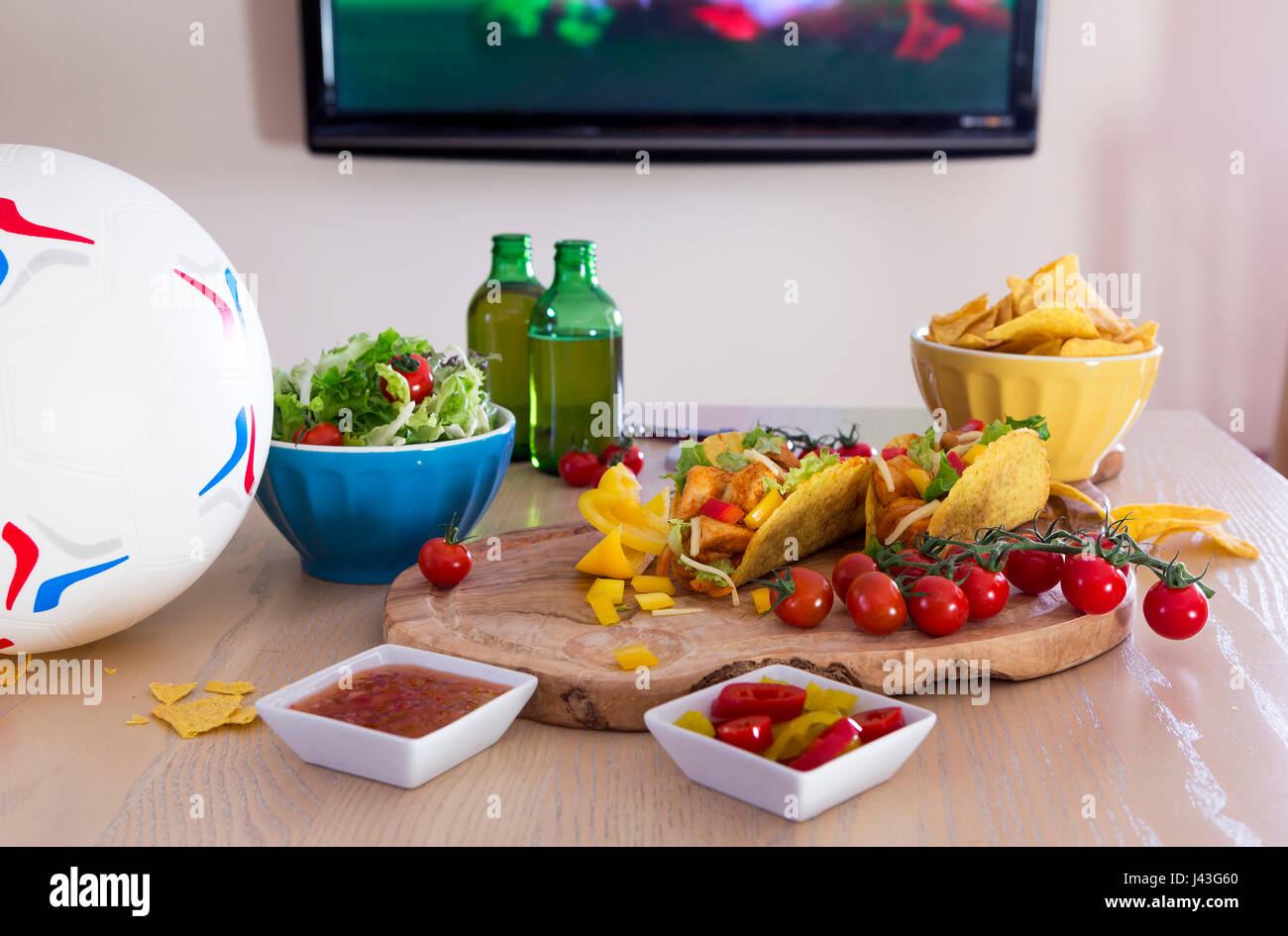 Mexican tacos and beer on a table with a football. There is a television in the background with sports showing. - Stock Image