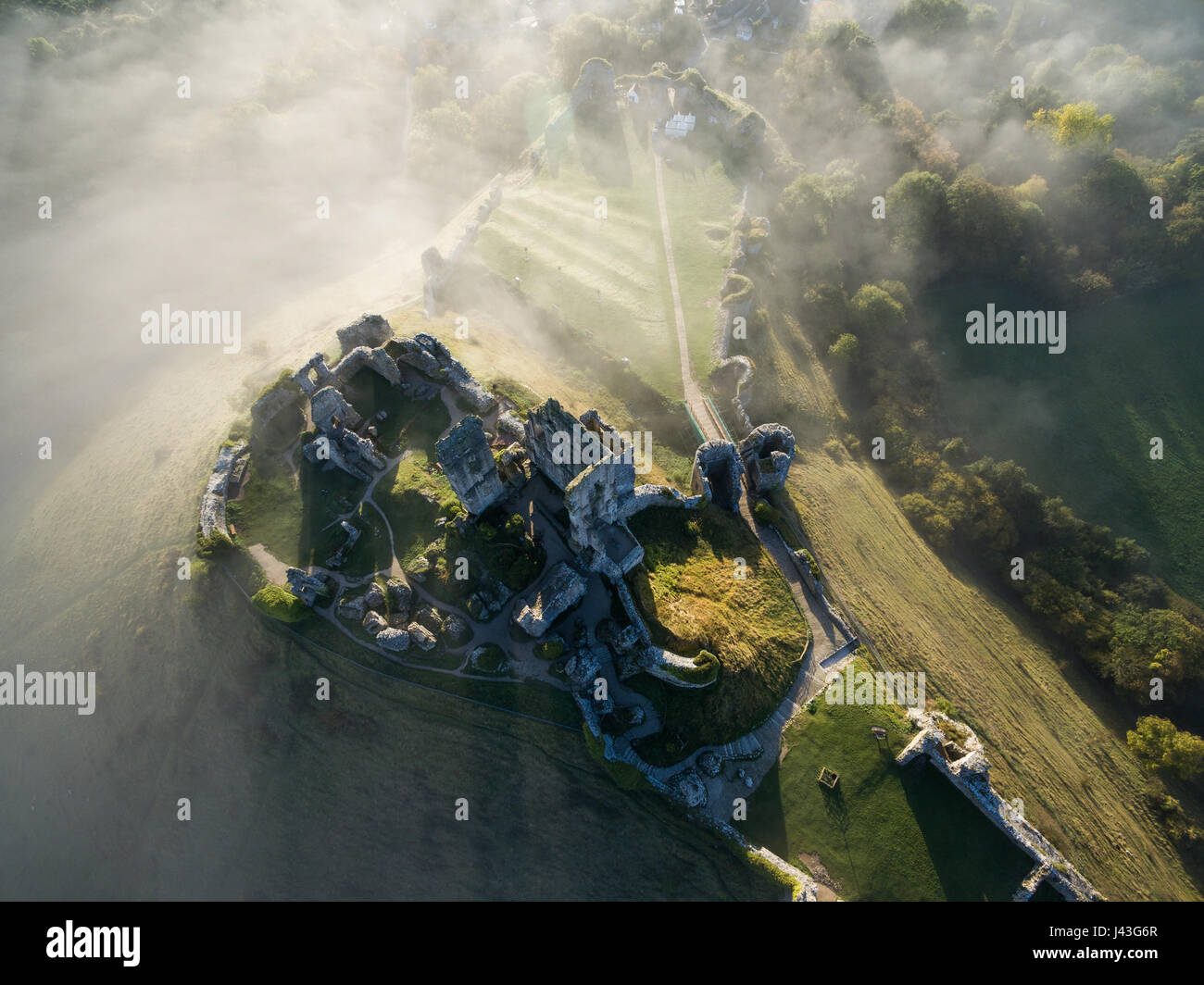 Aerial view of Corfe Castle at Sunrise on a misty morning - Stock Image